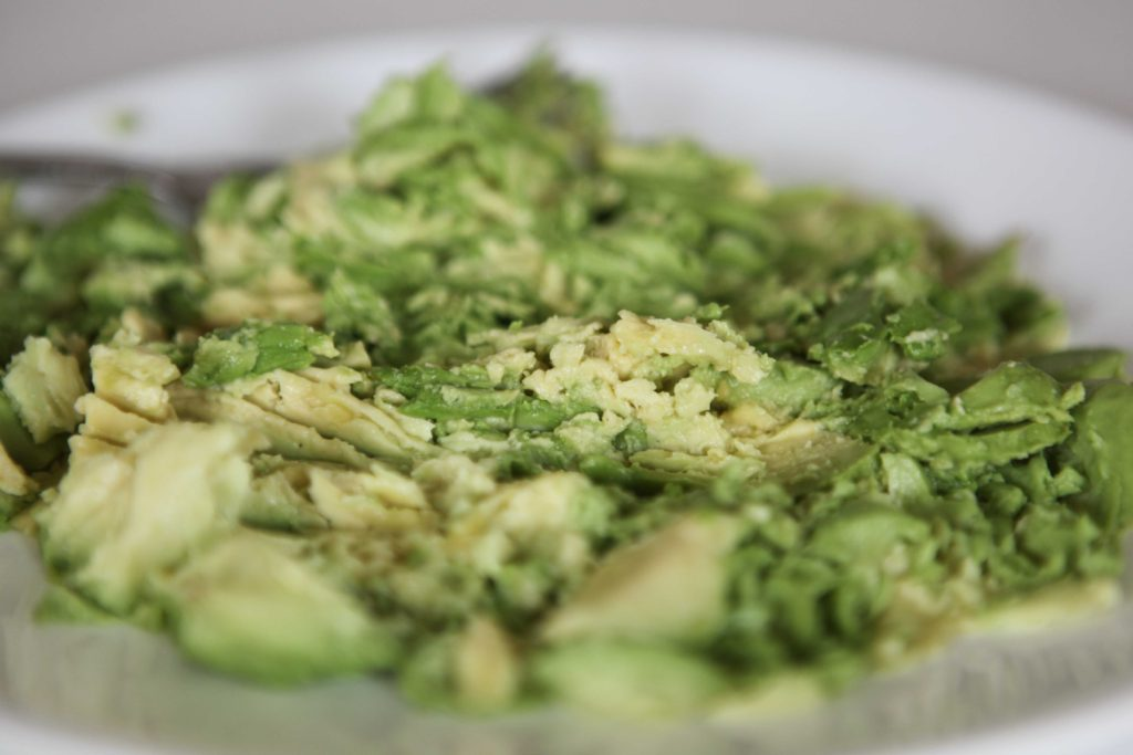 Peel the avocados, then mash them with a fork.