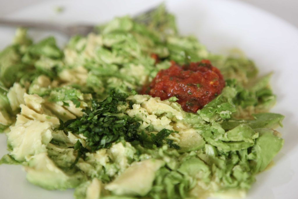 Add chopped cilantro, salt, lime juice, and salsa. Stir and mash it all together.