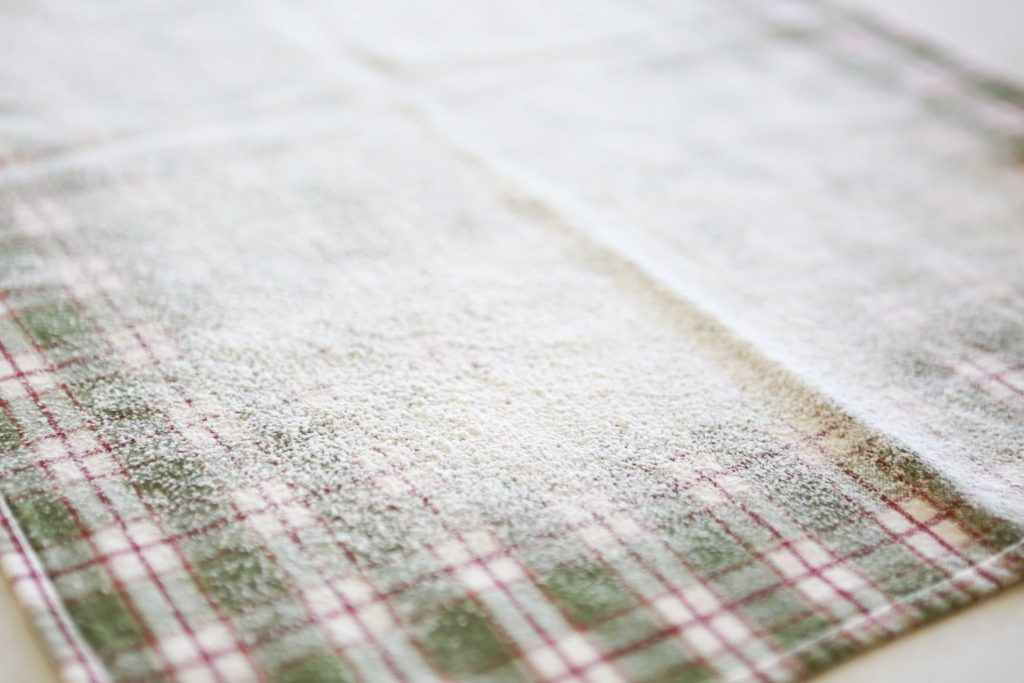 Sprinkle powdered sugar on a thin (lint-free) cotton kitchen towel.