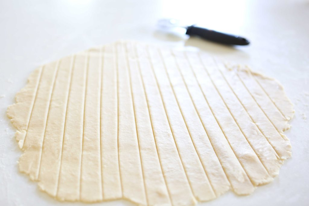 Using a pizza cutter or sharp knife, cut the circle of dough into long strips.