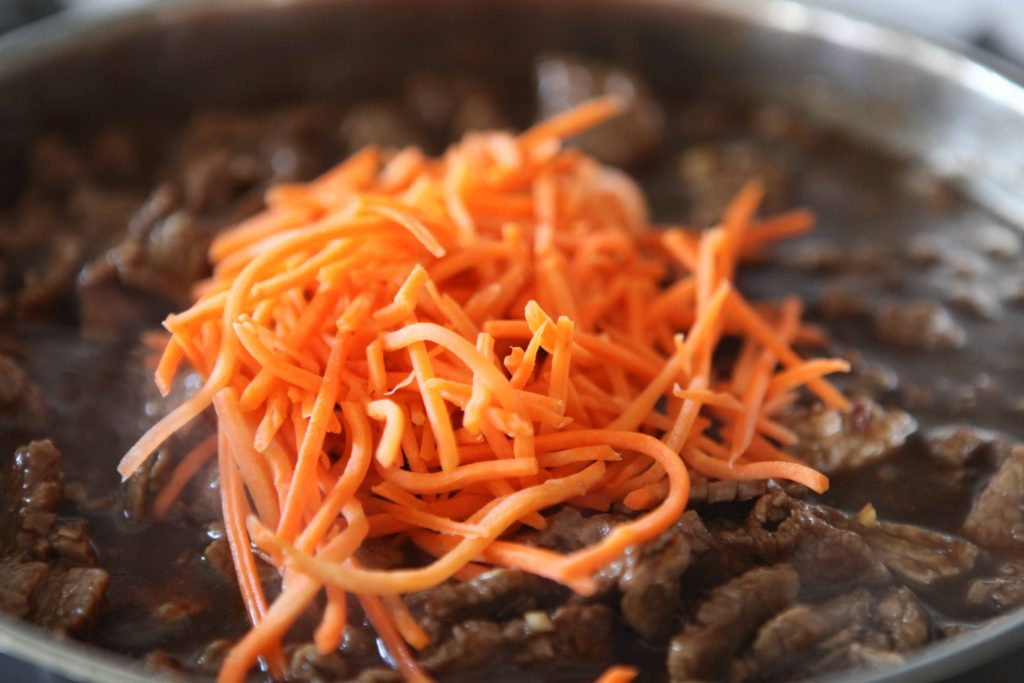 Stir in shredded carrots, and return to boil. Reduce heat to medium low.
