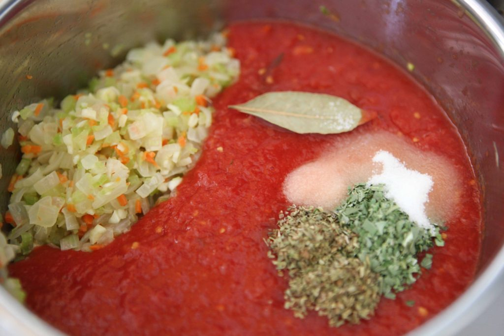 Add stewed tomatoes, basil, oregano, sugar, salt, pepper, and bay leaf to sauteed vegetables. Stir to combine.