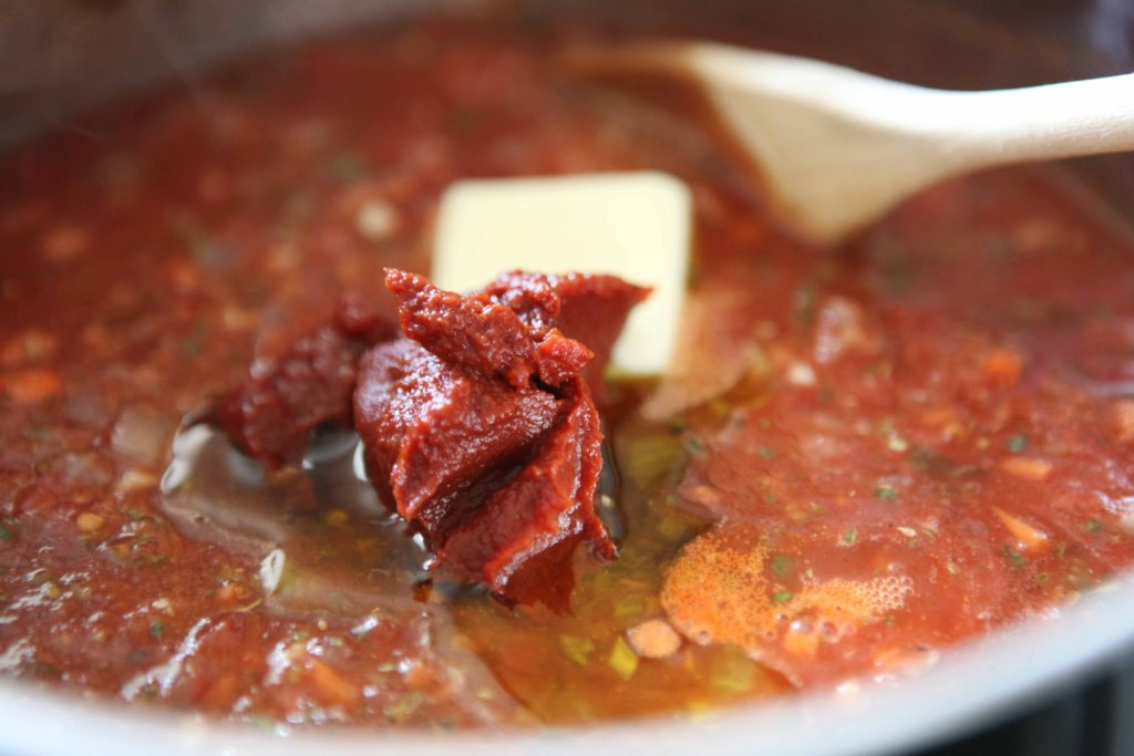 Stir in butter, remaining olive oil, and tomato paste, and bring sauce to a boil.