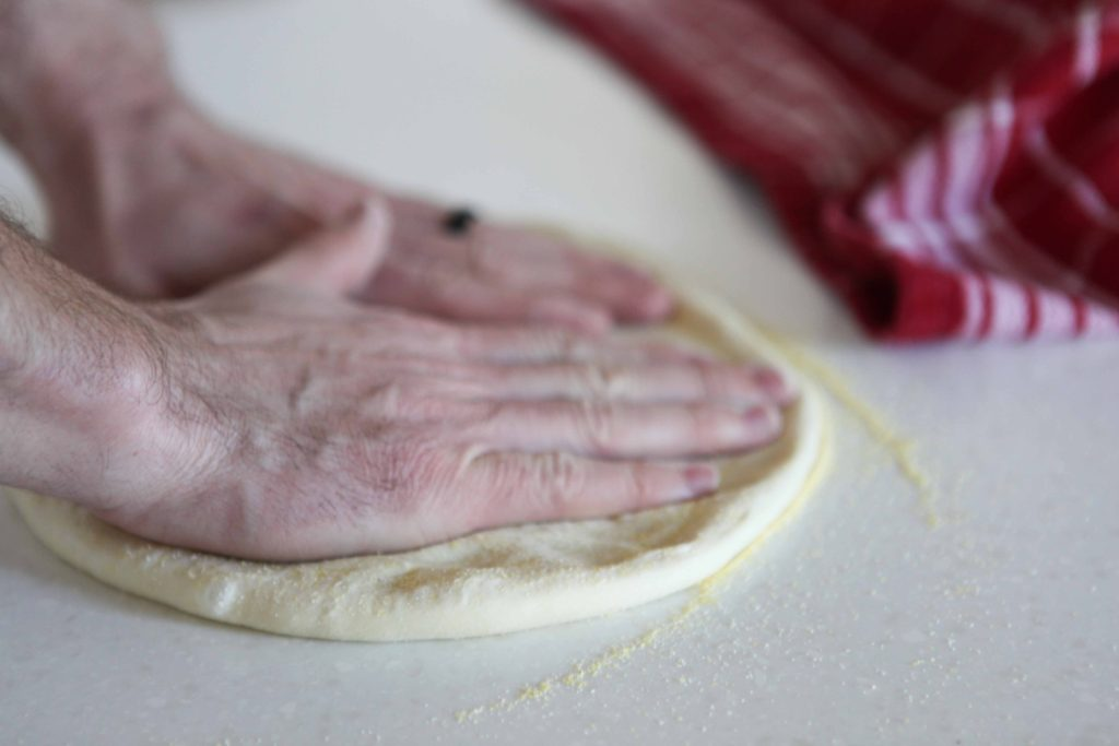 Use your palms to flatten the dough as your fingers push the circle out.