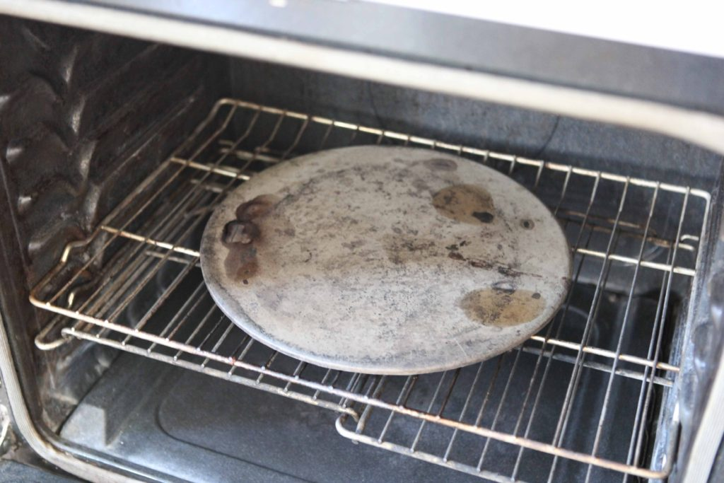 Place a large pizza stone on a rack situated about 5 inches from the oven floor.