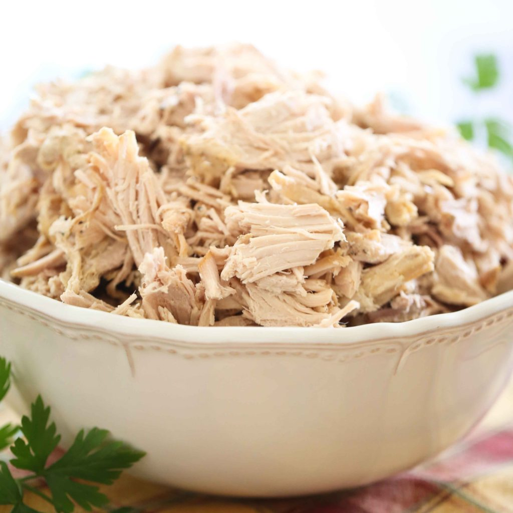 a large bowl full of cooked and shredded pork