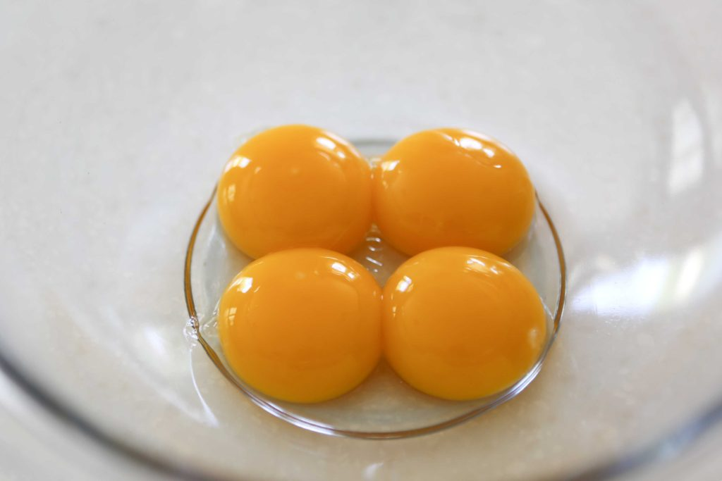 In a mixing bowl, start with 4 egg yolks You won't be using the whites in this recipe.
