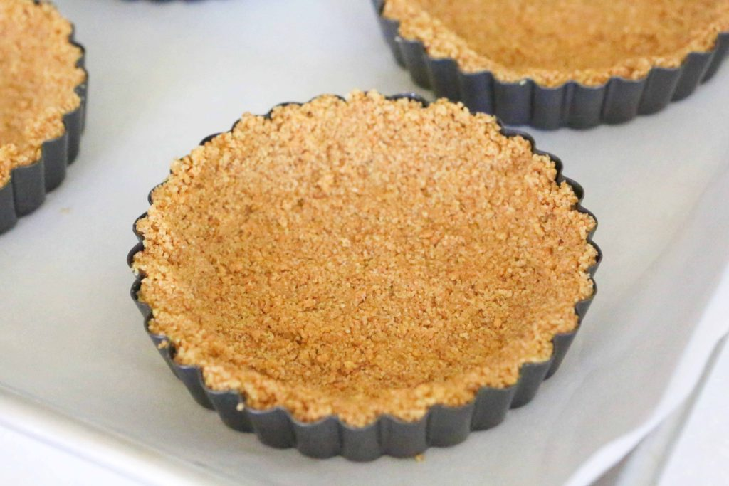 Place the tart crusts on a parchment-lined baking sheet, and bake at 350 degrees for 10 minutes to set them. Let them cool completely before filling.