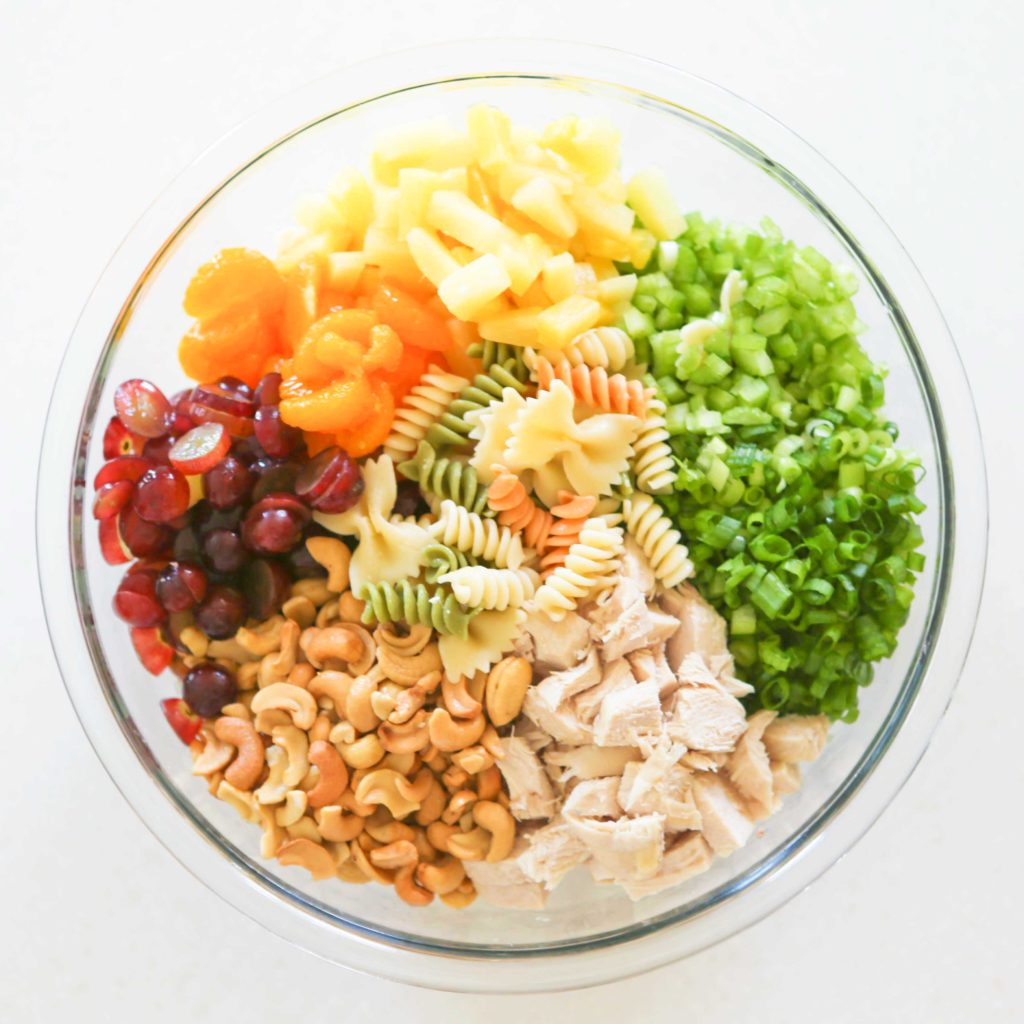 In a large mixing bowl, combine all the cooked, cooled pasta 3-4 cups cooked, diced chicken breast  2 bunches green onion, sliced 1 cup celery, chopped 1 (20 ounce) can pineapple tidbits, drained 1 can (11 ounce) mandarin oranges, drained 2 cups grapes, sliced 1 cup cashew pieces