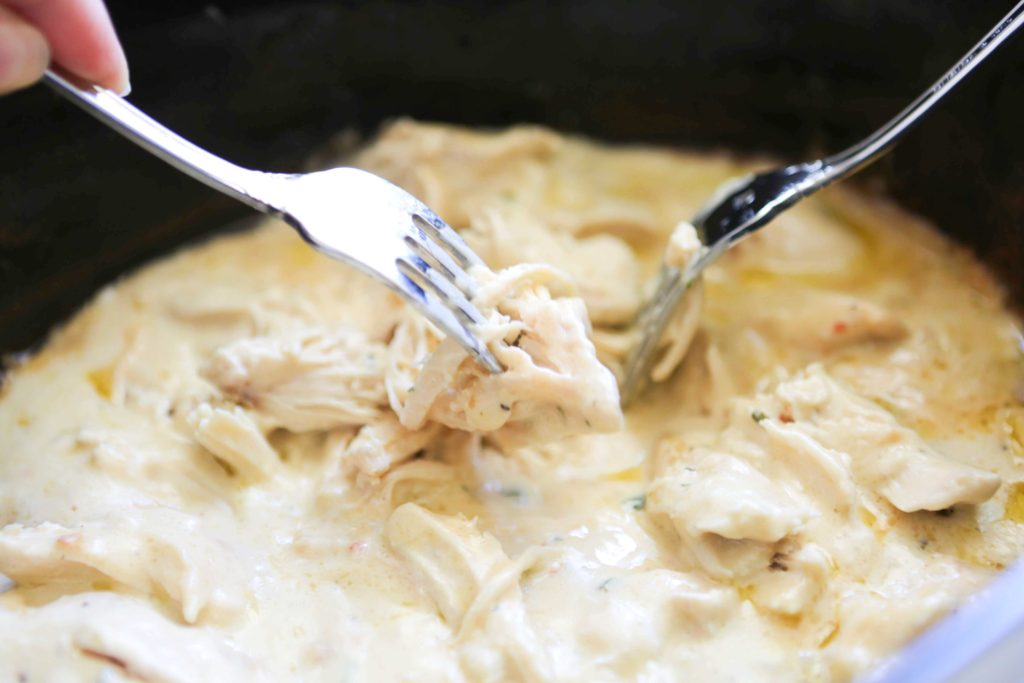 Make it even more simple. Use two forks to shred the chicken without removing it from the sauce.