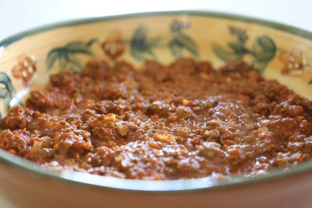 Spread half the meat sauce into bottom of prepared baking dish.