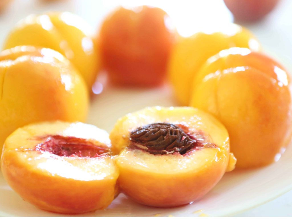 Fresh peaches, pealed, and sliced in half.