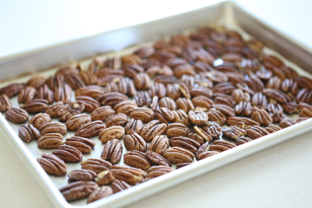 Arrange in a single layer on a baking sheet 7.5 ounces pecan halves Bake at 350 degrees for 10 minutes to lightly roast. Cool completely. (If you're planning on dipping some in chocolate, or using some plain ones, for decoration, add that many more to the pan.)