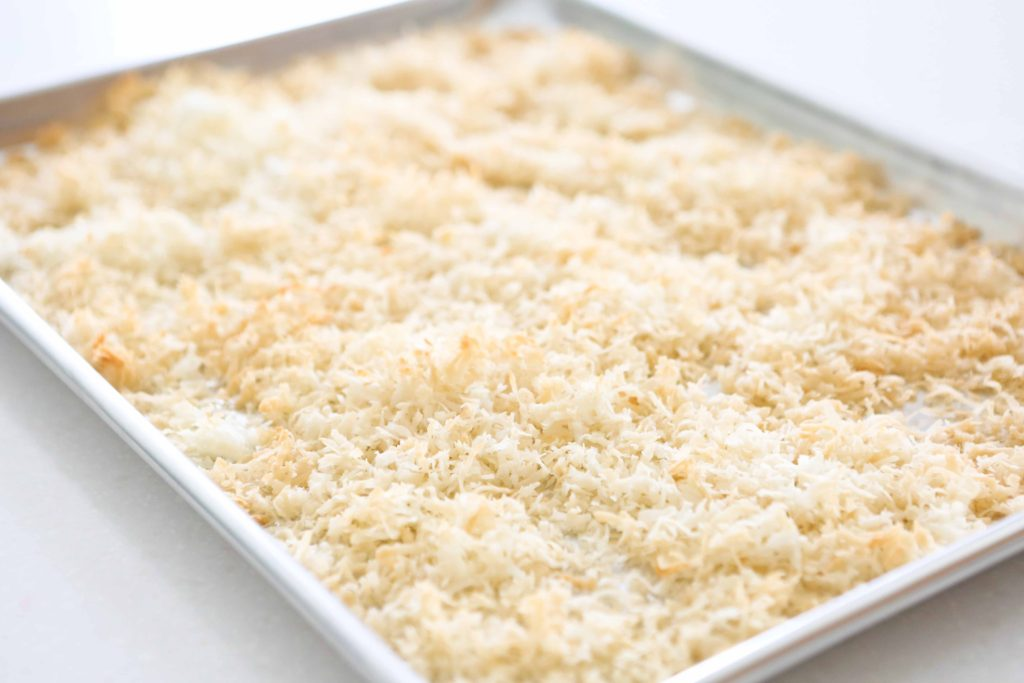 How to toast coconut - a cookie sheet with coconut in the process of being toasted