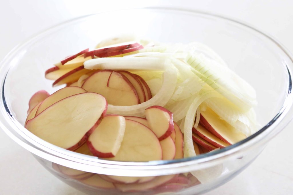 In a large mixing bowl, combine 3 pounds potatoes, scrubbed, sliced, and peeled 1 medium onion, sliced I try to slice the onion to the same thickness as the potatoes.