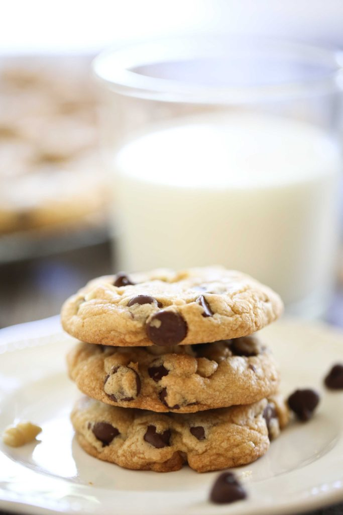 Three homemade Toll House Chocolate Chip Cookies with a glass of milk
