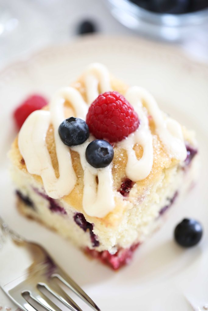 Red, White, and Blueberry Cake made with raspberries, blueberries, and cream cheese glaze