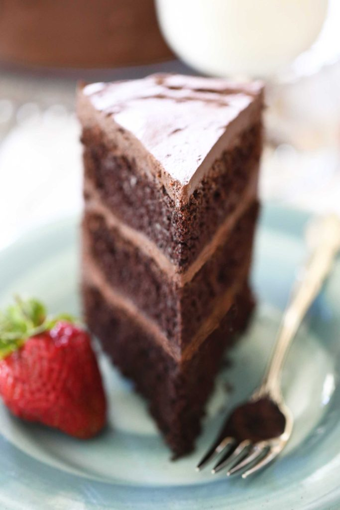 a large slice of homemade three-layer Chocolate Devil's Food Cake with Rich Chocolate Frosting with strawberry