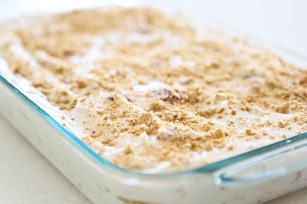 Sprinkling crushed graham crackers onto homemade Raspberry Ice Cream Cake