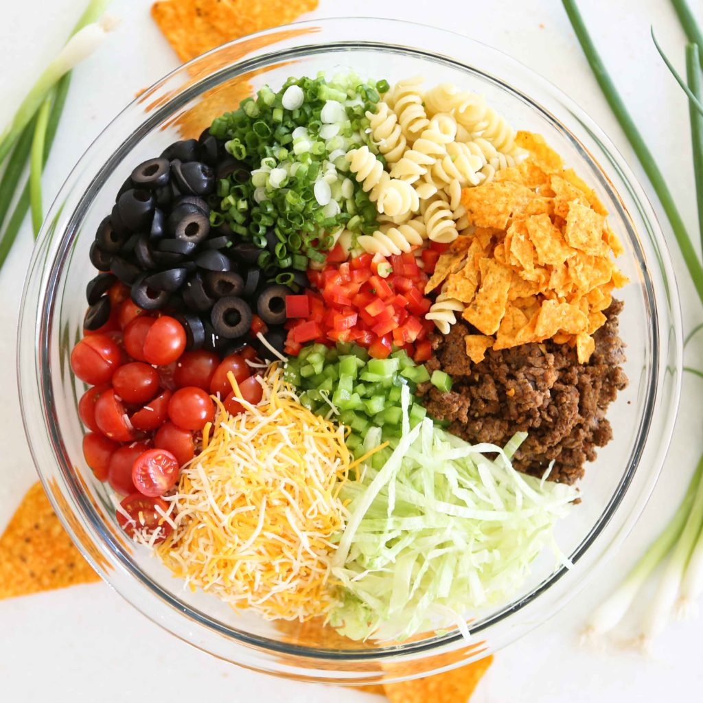 a bowl full of lettuce, taco-seasoned ground beef, crushed Doritos, green onions, cooked pasta, sliced olives, sliced tomatoes, green and red peppers, and shredded cheddar jack cheese for Taco Pasta Salad