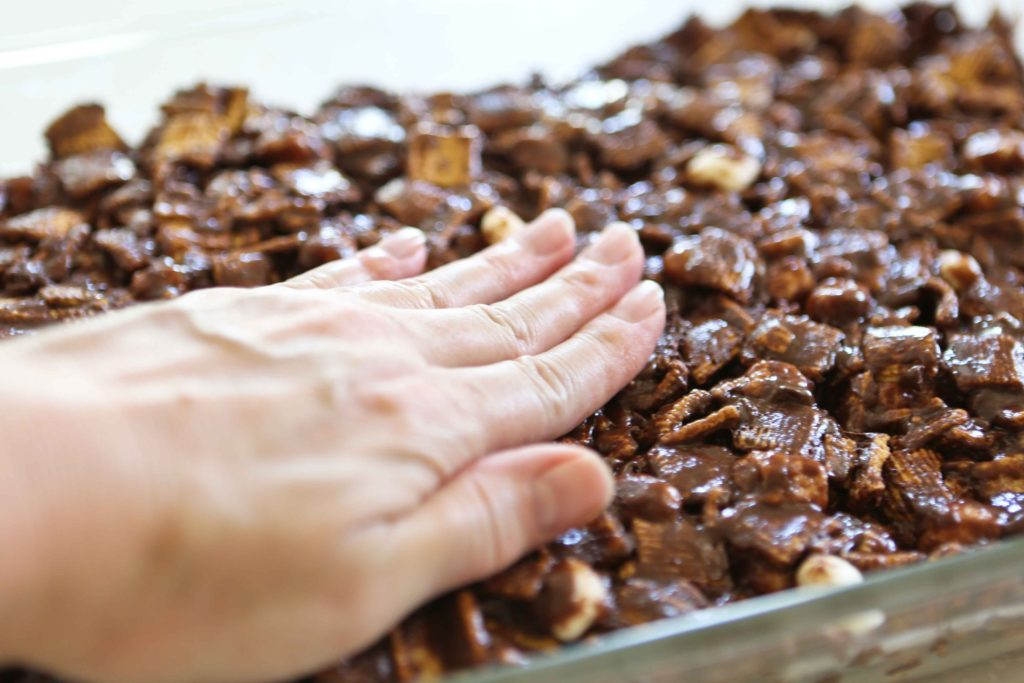 Indoor S'more Bars being pressed into pan