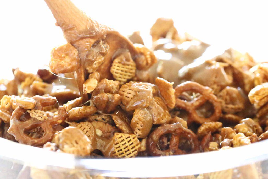 Stirring caramel into Nutty Caramel Chex Mix