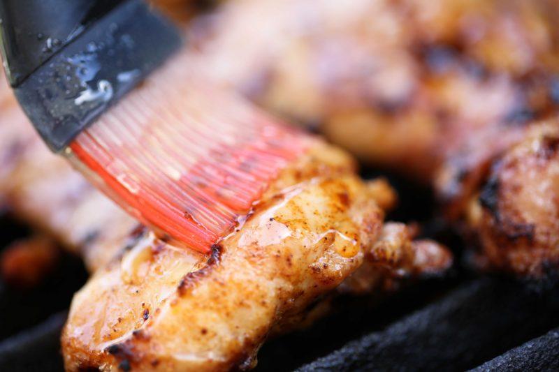 Applying honey glaze to spicy grilled chicken